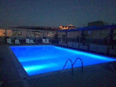 rooftop pool illuminated in blue at night